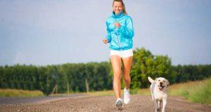Νεαρή γυναίκα τρέχει μαζί με σκύλο